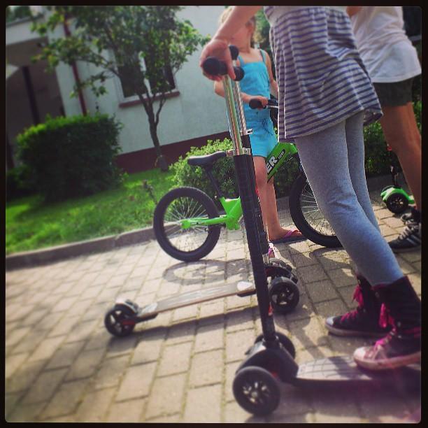 Dzieci na rowerkach biegowych i hulajnogach