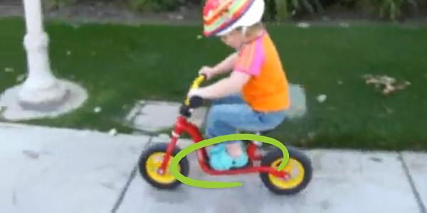 """Klatka z filmu """"Jada Riding Her Laufrad"""". Widać jak dziewczynka jadąc na rowerku biegowym Puky LR M trzyma nóżki na podnóżku"""